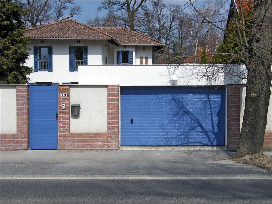 Elegáns kék garázskapu azonos megjelenésű kiskapuval